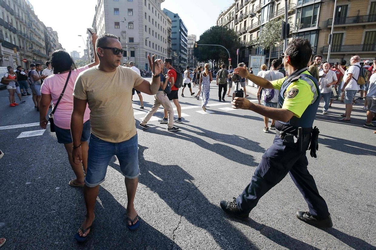 "A policeman asks people to move back near a cordoned off area after a van ploughed into the crowd, killing one person and injuring several others on the Rambla in Barcelona on August 17, 2017. Police in Barcelona said they were dealing with a ""terrorist attack"" after a vehicle ploughed into a crowd of pedestrians on the city's famous Las Ramblas boulevard on August 17, 2017. Police were clearing the area after the incident, which has left a number of people injured. / AFP PHOTO / Pau Barrena"