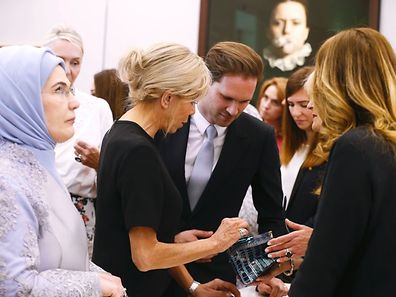 (LtoR) First Lady of Turkey Emine Gulbaran Erdogan, First Lady of France Brigitte Macron and First Gentleman of Luxembourg Gauthier Destenay are pictured during a visit of the First Ladies to a shop of Belgian fashion label Delvaux, on May 25, 2017, in Brussels, on the sidelines of the NATO (North Atlantic Treaty Organization) summit. / AFP PHOTO / BELGA / NICOLAS MAETERLINCK / Belgium OUT