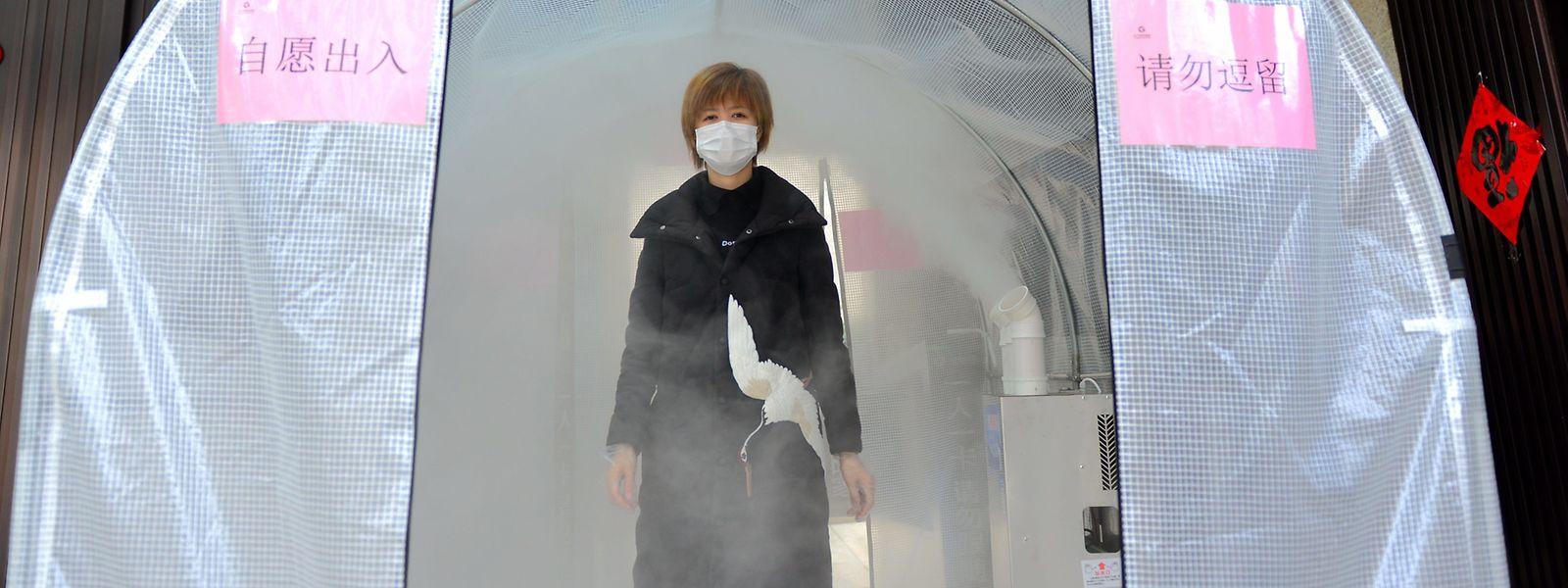 Une résidente de Luyang traverse un canal de désinfection. Le nouveau mode de calcul a fait exploser le nombre de cas de coronavirus en Chine.