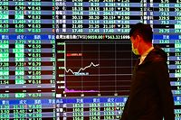 A man wearing a face mask walks past a screen showing stock prices on Taiwan�s Stock Exchange in Taipei on March 13, 2020. - Global stock markets suffered historic falls as panic spread on March 13 over the spiralling coronavirus crisis that has killed nearly 5,000 and infected sport, schools and society across the planet. (Photo by Sam Yeh / AFP)