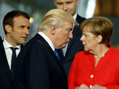 U.S. President Donald Trump (C) walks past French President Emmanuel Macron (L) and German Chancellor Angela Merkel on his way to his spot for a family photo during the NATO summit at their new headquarters in Brussels, Belgium May 25, 2017.  REUTERS/Jonathan Ernst