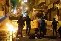 Demonstranten benutzen Baustoffplatten als Schilde bei Zusammenstößen mit der Polizei.