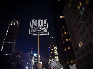 "TOPSHOT - An activist holds up a sign at the ""We Stand United"" rally on the eve of US President-elect Donald Trump's inauguration outside Trump International Hotel and Tower in New York on January 19, 2017 in New York. / AFP PHOTO / Bryan R. Smith"