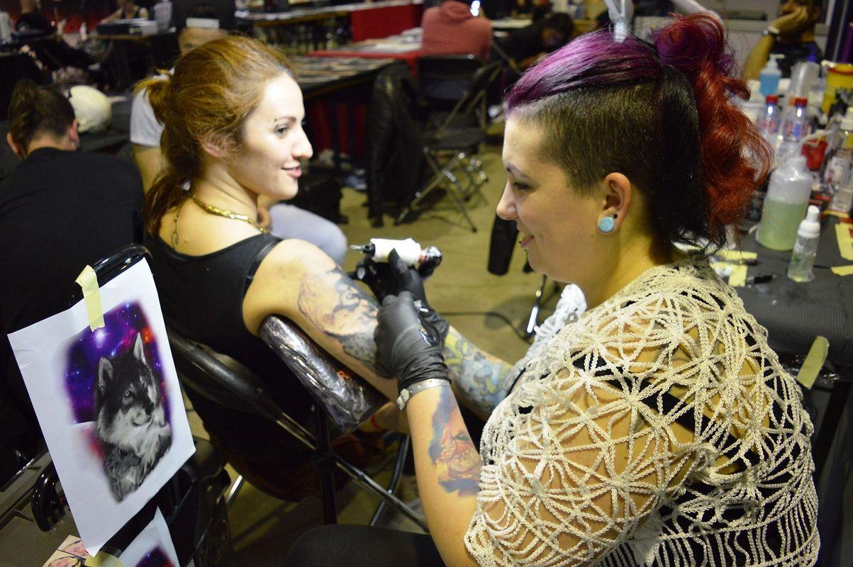 A tatuadora portuguesa Isabel Filipa Silva durante a realização de uma tatuagem realista na convenção no Luxemburgo.