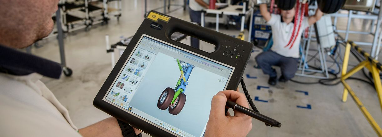 An employee uses a a tablet computer to view the landing gear of a Legacy 500 jet on the assembly line at the Embraer SA manufacturing plant in Sao Jose dos Campos, Brazil, on Wednesday, Oct. 7, 2015. United Airlines plans to order a fleet of 100-seat jetliners from either Embraer SA or Bombardier Inc. if it can agree on terms for a two-year contract extension with pilots in expedited bargaining. Photographer: Paulo Fridman/Bloomberg via Getty Images Ipad Arbeiter