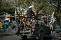 Taliban fighters patrol along a street in Kabul on August 31, 2021. - The Taliban joyously fired guns into the air and offered words of reconciliation on August 31, as they celebrated defeating the United States and returning to power after two decades of war that devastated Afghanistan. (Photo by Hoshang Hashimi / AFP)