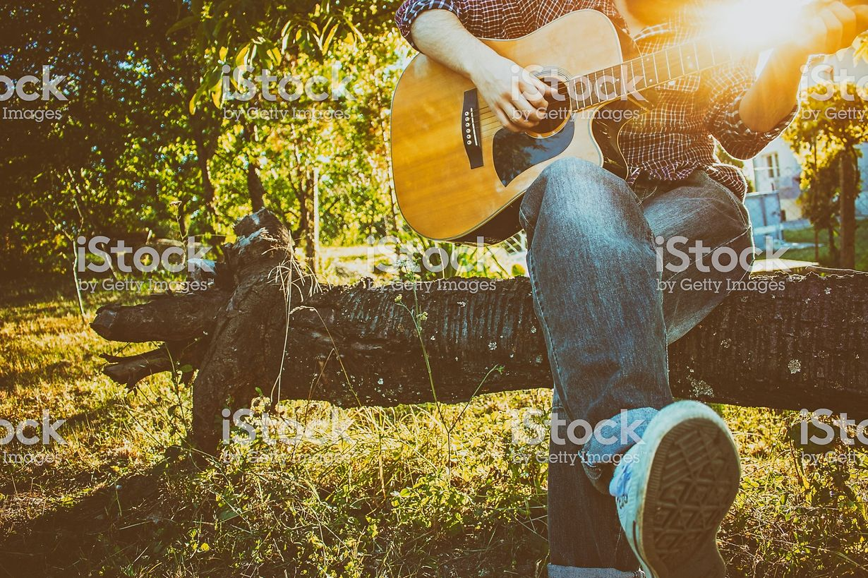 Bearded hipster playing acoustic guitar in nature