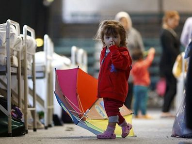 A migrant child walks through an temporary shelter in a sports hall in Hanau, Germany