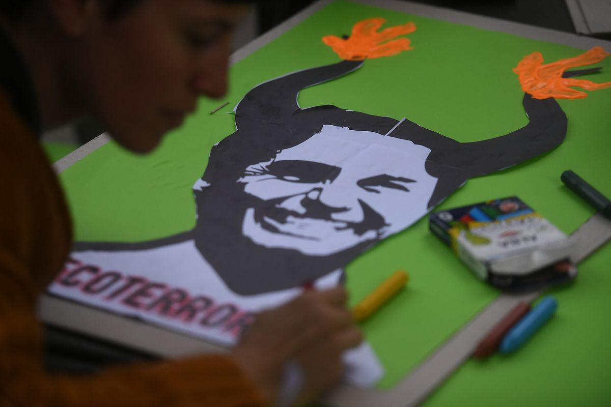 """Proteste in Buenos Aires: """"Ökoterror"""", steht auf einem Plakat unter der Abbildung vom brasilianischen Präsidenten Bolsonaro bei einem Protest vor der brasilianischen Botschaft."""