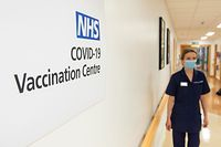 A nurse passes a sign indicating a Covid-19 Vaccination Centre at the Royal Free Hospital in London on December 7, 2020, ahead of the roll-out of the covid-19 vaccine tomorrow. - Britain has pre-ordered 40 million doses of the Pfizer-BioNTech vaccine in total, and is set to receive an initial batch of 800,000 to kickstart Tuesday's rollout. Elderly care home residents and their carers will be the very first in line, followed by those aged 80 and over and frontline health and care staff. (Photo by Dominic Lipinski / POOL / AFP)