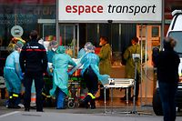 Medical staff carry a patient infected with the novel coronavirus (Covid-19) inside Nancy train station, eastern France, prior to his trasnfer into a medicalised TGV (high-speed train) on March 29, 2020. - Preparations for the evacuation of patients towards hospitals in the region of Nouvelle Aquitaine of 24 coronavirus-contaminated patients from Lorraine aboard a medicalised TGV began Sunday morning at Nancy station. (Photo by JEAN-CHRISTOPHE VERHAEGEN / AFP)