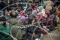 TOPSHOT - Migrants sit behind barbed wire fence at the buffer zone at Turkey-Greece border at Pazarkule, in Edirne district, on February 29, 2020. - Thousands of migrants stuck on the Turkey-Greece border clashed with Greek police on February 29, 2020, according to an AFP photographer at the scene. Greek police fired tear gas at migrants who have amassed at a border crossing in the western Turkish province of Edirne, some of whom responded by hurling stones at the officers. The clashes come as Greece bolsters its border after Ankara said it would no longer prevent refugees from crossing into Europe following the death of 33 Turkish troops in northern Syria. (Photo by BULENT KILIC / AFP)