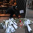 TOPSHOT - A man lights a candle in tribute to the victims of a deadly shooting the day before in central Strasbourg, on December 12, 2018. - Hundreds of police and anti-terror forces hunted on December 12, 2018 for a gunman who shot dead several people and wounded a dozen at a Christmas market in Strasbourg, with the suspect known to police and thought to be a religious extremist. (Photo by Patrick HERTZOG / AFP)
