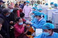 TOPSHOT - This photo taken on April 12, 2021 shows people receiving the China National Biotec Group (CNBG) Covid-19 coronavirus vaccine in China's southwestern Chongqing. (Photo by STR / AFP) / China OUT