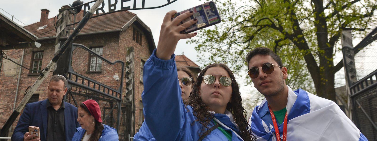 """Vor dem ikonischen Tor mit dem """"Arbeit macht frei""""-Schriftzug lassen sich Hunderte fotografieren, mit ernstem Gesicht. Nur wenige lächeln oder machen Selfies."""