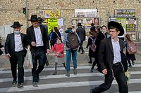 People cross a street in an ultra-Orthodox Jewish neighbourhood in Jerusalem, on March 11, 2021. - Tensions between mainstream Israelis and ultra-Orthodox Jews, or haredim, have roiled throughout the COVID-19 pandemic. Refusals by top rabbis to close religious schools and street-packing haredi funerals that ignored restrictions on gatherings infuriated the public, which blamed haredi defiance for extended lockdowns. But beyond hostilities, experts said the pandemic has also ignited an internal debate within the ultra-Orthodox community over whether its conduct during the crisis was justified. (Photo by MENAHEM KAHANA / AFP)