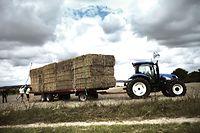 """De la paille est chargée sur un tracteur le 27 juillet 2011 à Bray-sur-Seine, en Seine-et-Marne où une caravane de 60 tracteurs se ravitaille. Les agriculteurs de l'Ain vont y trouver, après un périple de plus de 300 kilomètres, 1.000 tonnes de paille à rapporter dans leurs élevages affectés par la sécheresse en mai dernier, dans le cadre d'un """"convoi de solidarité"""". AFP PHOTO / JEFF PACHOUD"""