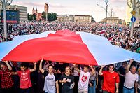 TOPSHOT - Belarus opposition supporters hold a giant former white-red-white flag of Belarus used in opposition to the government, during a demonstration in central Minsk on August 16, 2020. - The Belarusian strongman, who has ruled his ex-Soviet country with an iron grip since 1994, is under increasing pressure from the streets and abroad over his claim to have won re-election on August 9, with 80 percent of the vote. (Photo by Sergei GAPON / AFP)