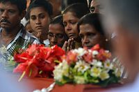 Mourners stand beside a coffin of a bomb blast victim at a funeral service at St Sebastian's Church in Negombo on April 23, 2019, two days after a series of bomb blasts targeting churches and luxury hotels in Sri Lanka. - Sri Lanka began a day of national mourning on April 23 with three minutes of silence to honour nearly 300 people killed in suicide bomb blasts that have been blamed on a local Islamist group. (Photo by ISHARA S. KODIKARA / AFP)