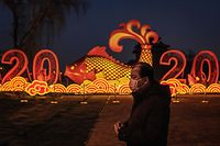TOPSHOT - A man wears a protective facemask to help stop the spread of a deadly SARS-like virus which originated in the central city of Wuhan, as he walks on the outskirts of the Forbidden City and a New Year instalation displaying a fish and the number 2020 in Beijing on January 25, 2020. - China announced it will close a section of the Great Wall and other famous Beijing landmarks to control the spread of a deadly virus that has infected hundreds of people across the country. (Photo by NICOLAS ASFOURI / AFP)