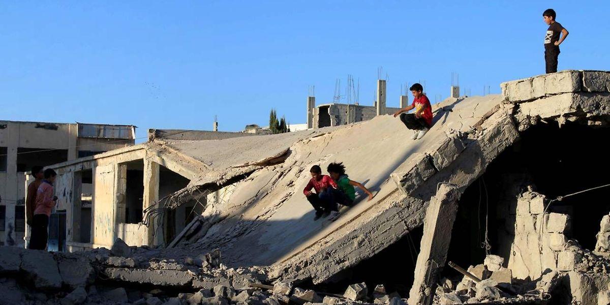 Des enfants syriens jouent sur les ruines de Daraa, au sud-ouest de la Syrie.