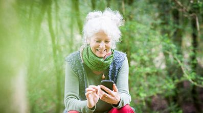 Mature female gardener taking a break looking at smartphone
