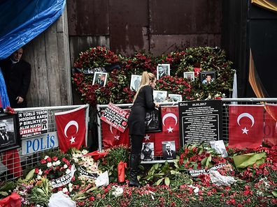 A woman lays flowers at a makeshift memorial in front of the Reina nightclub in Istanbul on January 17, a day after Turkish police arrested the suspected attacker.