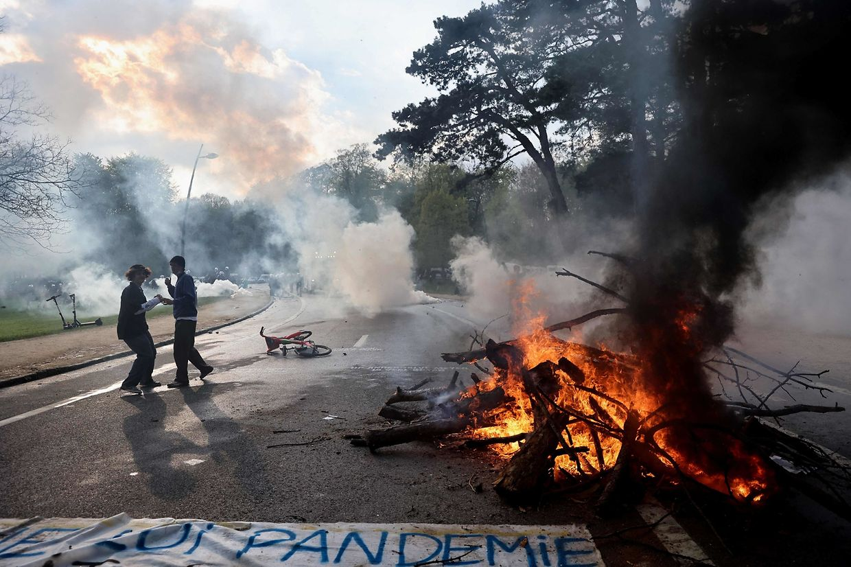 Two protesters are surrounded by tear gas during clashes with riot police at the Bois de La Cambre park in Brussels, on May 1, 2021, during the second edition of the illegal 'La Boum - L'Abime' festival, a protest against the Covid-19 health restrictions. (Photo by Kenzo TRIBOUILLARD / AFP)