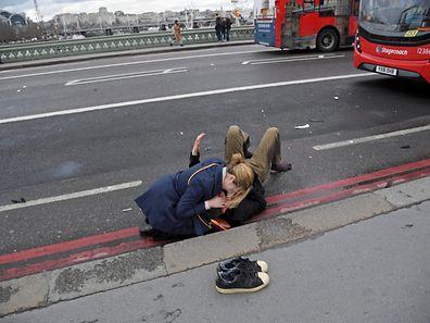 Une femme assiste un blessé sur le pont de Westminster