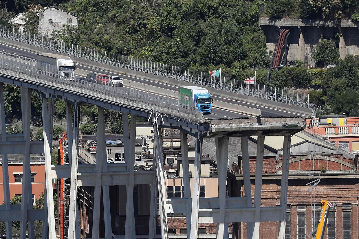 This view taken on August 15, 2018, shows abandoned vehicles on the Morandi motorway bridge the day after a section collapsed in the north-western Italian city of Genoa. - At least 38 people were killed on August 14, when the giant motorway bridge collapsed in Genoa in northwestern Italy. The collapse, which saw a vast stretch of the A10 freeway tumble on to railway lines in the northern port city, was the deadliest bridge failure in Italy for years, and the country's deputy transport minister warned the death toll could climb further. (Photo by Valery HACHE / Piero CRUCIATTI / AFP / AFP)