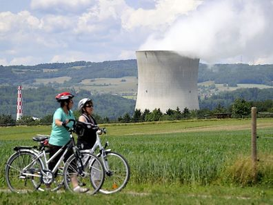 (FILES) This file photo taken on May 22, 2011 shows two women walking in front of Leibstadt nuclear power plant near Leibstadt, northern Switzerland. ?Switzerland on May 21, 2017, votes on whether to overhaul its national energy policy, with proposals on phasing out nuclear energy and boosting reliance on renewables, in the latest referendum in the country's direct democracy system. / AFP PHOTO / FABRICE COFFRINI