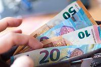 ARCHIV - 04.12.2018, Sachsen, Dresden: ILLUSTRATION - Eine Frau hält eine Geldbörse mit Banknoten in der Hand. Trotz riesiger Hilfsprogramme für die Wirtschaft in der Corona-Krise, erwarten Ökonomen keine Inflation. Foto: Monika Skolimowska/dpa-Zentralbild/dpa +++ dpa-Bildfunk +++
