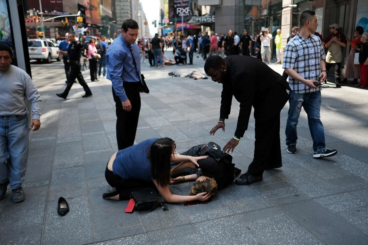 EDITORS NOTE: Graphic content / People attend to an injured person moments after a car plunged into them in Times Square in New York on May 18, 2017.  A car plowed into a crowd of pedestrians in New York's bustling Times Square, leaving one person dead and at least 12 other injured in what officials said was an accident.  / AFP PHOTO / Jewel SAMAD