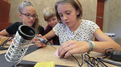Konzentriert arbeiten Julie, Philip und Lou (v.l.n.r.) an ihrer Teslaspule.