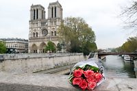 ECO CLEMENT/UPI/MAXPPP - Flowers are laid before Notre Dame Cathedral after a giant fire was put down in Paris 16 April 2019. French President Emmanuel Macron vowed to rebuild the 13th century building that welcomes tens of millions of worshippers and tourists per year. Photo by Eco Clement/UPI (MaxPPP TagID: maxbestof079521.jpg) [Photo via MaxPPP]