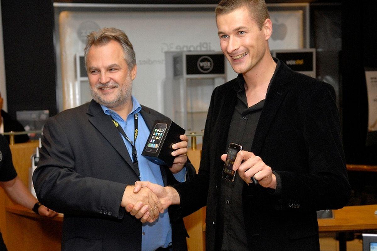 Jean-Claude Bintz (links) überreicht dem ersten Luxemburger Kunden das begehrte iPhone.