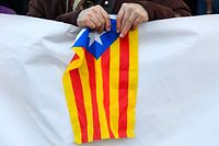 A protester holds a Catalan pro-independence Estelada flag during a protest against the trial of jailed Catalan separatists at the Supreme Court in Madrid on February 12, 2019. - Twelve former Catalan leaders go on trial at Spain's Supreme Court for their role in a failed 2017 bid to break away from Spain. (Photo by GABRIEL BOUYS / AFP)
