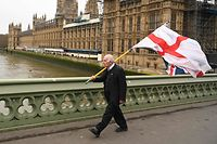 (FILES) In this file photo taken on January 31, 2020 A man carries a flag of St George, the English national flag, along with a Union Flag as he walks along Westminster Bridge by the Houses of Parliament in London. - The United Kingdom has endured in one form or another for hundreds of years but between Brexit and the coronavirus, the country is creaking and some suggest it may be on the verge of breaking up entirely. (Photo by Glyn KIRK / AFP)