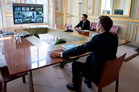 French President Emmanuel Macron (R) attends a video conference call with members of the European Council at the Elysee Palace in Paris, on March 26, 2020, to discuss coordination of EU efforts to tackle the outbreak of COVID-19 (novel coronavius), as well as other issues, including foreign affairs, digital policy and enlargement. - EU leaders will try on March 26 to unify their scattershot response to the COVID-19 epidemic, after hardest-hit Spain, France and Italy called for joint borrowing to share the economic burden. Hundreds of millions of the bloc's citizens are holed up at home, during lockdowns imposed to help slow the pandemic that has killed more than 20,000 Europeans and crippled business life. (Photo by Ian LANGSDON / POOL / AFP)