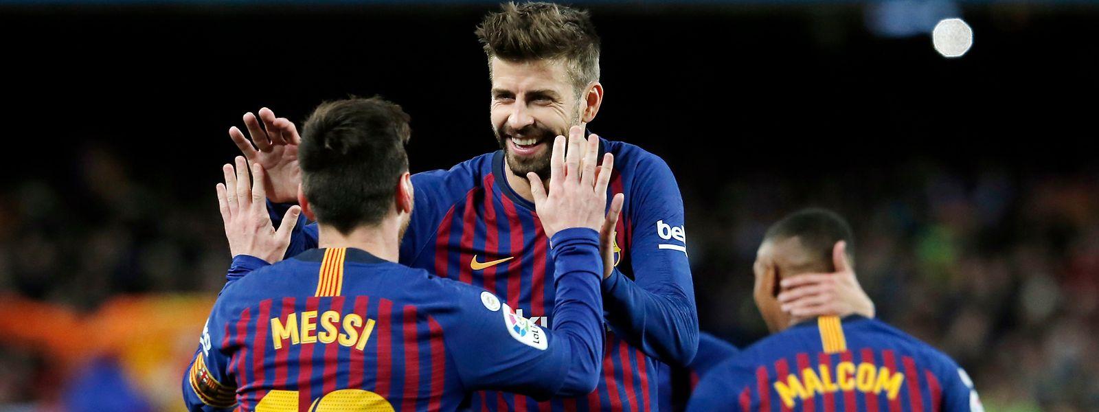Lionel Messi congratulé par Gerard Piqué, deux atouts d'un Barça conquérant ce mercredi soir à Old Trafford