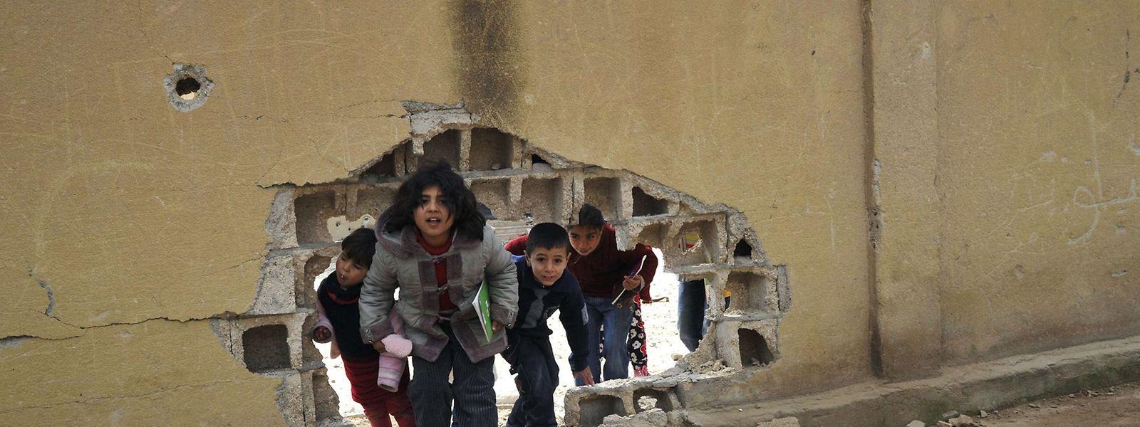 Nach mehr als vier Monaten des Kämpfens der Versuch zurück zum Alltag. Schüler in Kobane benutzen eine zerbomte Wand als Eingang in der Schule.