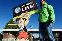 """(FILES) In this file photo taken on September 25, 2015 an activist holds up a sign reading """"No more lies"""" during a protest of environmental watchdog Greenpeace in front of the headquarters of German car maker Volkswagen in Wolfsburg, central Germany. - Car behemoth Volkswagen will face a German court on September 30, 2019 as hundreds of thousands of owners of manipulated diesel cars demand compensation four years after the country's largest post-war industrial scandal erupted. (Photo by John MACDOUGALL / AFP)"""