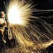 TOPSHOT - This picture taken on January 17, 2018 shows a Chinese worker cutting steel in Qingdao in China's eastern Shandong province on January 18, 2018. China's economy grew a forecast-beating 6.9 percent in 2017, picking up steam for the first time since 2010 despite its battles against a massive debt and polluting factories, official data showed on January 18. / AFP PHOTO / - / China OUT