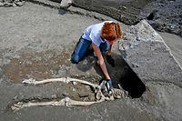 Pechvogel des Jahrtausends: Archäologin Valeria Amoretti arbeitet am Skelett eines Mannes, der auf der Flucht vor der Vulkanasche in Pompeji von einem umherfliegenden Trümmerteil eines Hauses erschlagen wurde.