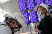 A woman from the Netherlands and her friend from Britain stand next to the display flight information at Josep Tarradellas Barcelona-El Prat Airport, as a case of novel coronavirus has been confirmed in Barcelona, Spain February 26, 2020. REUTERS/Nacho Doce - RC2E8F90FQYS