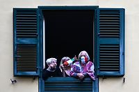 TOPSHOT - People with protective masks look from their windows at artists performing in the courtyard of a popular apartment building for the show Sotto lo Stesso Cielo tour (Under the Same Sky tour) in San Basilio suburbs of Rome on April 18, 2020, during the country's lockdown aimed at stopping the spread of the COVID-19 (new coronavirus) pandemic. (Photo by Alberto PIZZOLI / AFP)