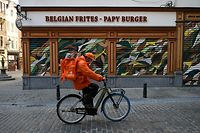 A deliverer, wearing a face mask, rides in front of a closed restaurant, due to national restrictions as Belgium is facing a second wave of the covid-19 pandemic caused by the novel coronavirus, in Brussels on November 6, 2020. (Photo by JOHN THYS / AFP)