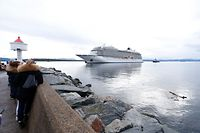 The cruise ship Viking Sky, that ran into trouble in stormy seas off Norway, reaches the port of Molde under its own steam on March 24, 2019. - Escorted by tugboats, the Viking Sky arrived at the port of Molde. Nearly a third of its 1,373 passengers and crew had already been airlifted off the ship after it lost power along a stretch of Norwegian coastline notorious for shipwrecks. (Photo by Svein Ove EKORNESVAAG / NTB scanpix / AFP) / Norway OUT