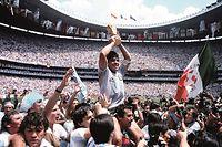 Diego Maradona reißt den WM-Pokal in die Höhe.