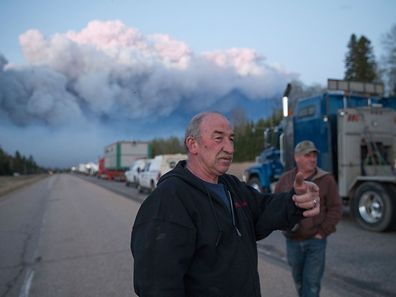 FORT MCMURRAY, AB - MAY 05: Drivers wait for clearance to take firefighting supplies into town on May 05, 2016 outside of Fort McMurray, Alberta. Wildfires, which are still burning out of control, have forced the evacuation of more than 80,000 residents from the town.   Scott Olson/Getty Images/AFP == FOR NEWSPAPERS, INTERNET, TELCOS & TELEVISION USE ONLY ==